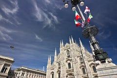 Fachada de Milan Cathedral con las banderas en el cielo azul Banderas que agitan en el cielo azul imágenes de archivo libres de regalías