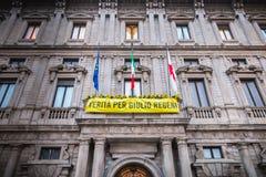 A fachada de Milan City Hall, de uma bandeira amarela ou dela é escrita em italiano - verdade para Giulio Regeni imagens de stock royalty free