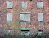 A fachada de um derelict abandonou a construção industrial do tijolo velho com o quebrado embarcado acima das janelas de deterior foto de stock