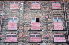 A fachada de um derelict abandonou a construção industrial do tijolo velho com o vermelho pintado quebrado embarcado acima das ja imagens de stock royalty free