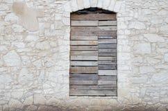 Fachada de uma casa de pedra velha abandonada da pedra calcária com embarcado acima fotografia de stock royalty free