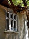 Fachada de uma casa de um só andar abandonada com janelas quebradas e o telhado caído, dia de verão foto de stock