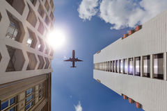 A fachada de uma construção alta com um avião no céu azul Imagens de Stock Royalty Free