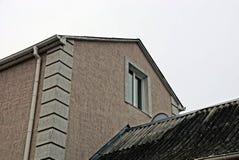 Fachada de uma construção com um telhado da porta e de ardósia da janela Foto de Stock