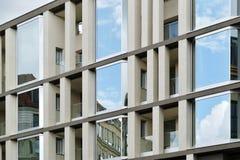 A fachada de uma construção moderna com algumas janelas que refletem o céu Foto de Stock