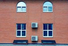A fachada de uma construção de tijolo com janelas e condicionamento de ar Imagens de Stock Royalty Free