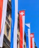 Fachada de un edificio adornado con las banderas de Zurich y de Switzerl Fotos de archivo