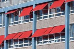 Fachada de un edificio con las sombrillas rojas Imágenes de archivo libres de regalías