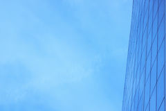 A fachada de vidro de um arranha-céus com uma reflexão de espelho de janelas do céu Imagem de Stock Royalty Free
