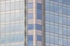 A fachada de vidro de um arranha-céus com uma reflexão de espelho de janelas do céu Fotos de Stock