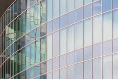 A fachada de vidro de um arranha-céus com uma reflexão de espelho de janelas do céu Imagens de Stock Royalty Free