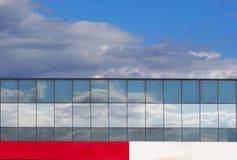 Fachada de vidro que reflete o céu com um painel branco e vermelho abaixo Imagens de Stock Royalty Free