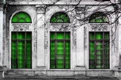 Fachada del edificio abandonado viejo con tres ventanas arqueadas grandes de vidrio verde Fondo monocromático Imágenes de archivo libres de regalías