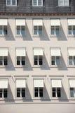Fachada del edificio gris con el toldo y la sombra blancos Imagenes de archivo