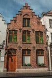 Fachada del ladrillo de la casa en el estilo típico de la región de Flanders's en la calle de Brujas Imagen de archivo libre de regalías