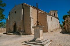 Fachada dianteira da igreja de pedra em um dia ensolarado com cruzeiro do primeiro plano, em Menerbes imagens de stock royalty free