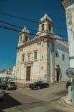 Fachada do mármore da igreja na frente da rua com casas velhas imagens de stock royalty free