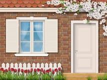 Fachada do tijolo com as tulipas da cerca da janela ilustração royalty free