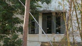 Fachada exterior de uma construção cercada por árvores video estoque