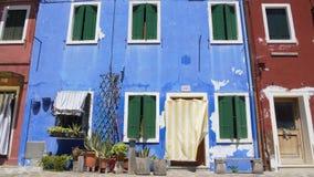 Fachada gasto da casa colorida azul decorada com os potenciômetros de flor agradáveis, pobreza filme