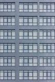 Fachada gris oscuro del edificio con las ventanas grandes grises Bloque de apartamentos Foto de archivo libre de regalías