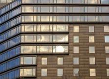 Fachada moderna abstracta de la casa de oficina con las ventanas en la reflexión del cielo Fotografía de archivo libre de regalías