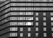 Fachada moderna abstracta de la casa de oficina con las ventanas en la reflexión del cielo Imágenes de archivo libres de regalías
