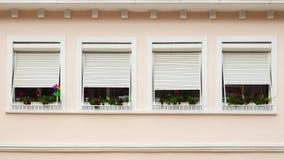 Fachada rosada con las ventanas adornadas con las flores Imagen de archivo libre de regalías