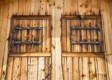 Fachada rústica de uma casa de madeira com obturadores de madeira Fotografia de Stock Royalty Free
