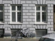 Fachada velha da casa da cidade com uma bicicleta sob Windows Fotografia de Stock Royalty Free