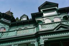 Fachada victoriana angulosa de la mansión, torrecilla contra el cielo azul fotografía de archivo
