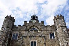 Fachada vieja con una torre de reloj, las torrecillas, y los almenajes Fotos de archivo libres de regalías