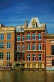 Fachada vieja de los edificios de ladrillo a lo largo del canal y del cielo azul soleado en Amsterdam Fotos de archivo