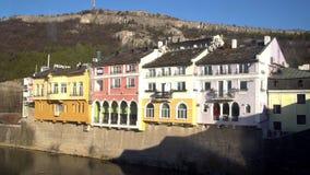 Fachadas constructivas coloridas hist?ricas en un d?a soleado en Lovech, Bulgaria Con el r?o de Osam en el frente y la monta?a en metrajes
