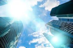 Fachadas de vidro do arranha-céus em um dia ensolarado brilhante com raios de sol no céu azul Construções modernas no negócio de  Fotos de Stock