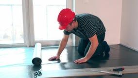 Facharbeitermann mit rotem Sturzhelm legen Unterbodenbelagmatte im neuen Raum stock video footage