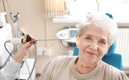 Facharzt für Hals- und Ohrenleiden, der ältere Frau \ 's-Ohr mit HNOteleskop im Krankenhaus überprüft lizenzfreie stockfotos