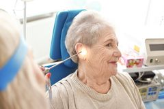 Facharzt für Hals- und Ohrenleiden, der ältere Frau \ 's-Ohr mit HNOteleskop im Krankenhaus überprüft stockbilder