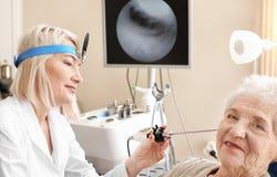 Facharzt für Hals- und Ohrenleiden, der das Ohr der älteren Frau mit HNOteleskop im Krankenhaus überprüft stockfotos