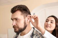 Facharzt für Hals- und Ohrenleiden, der Hörgerät in das Ohr des Mannes auf hellen Hintergrund einsetzt lizenzfreie stockfotografie