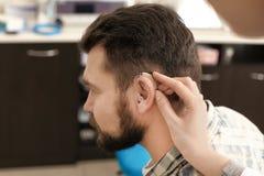 Facharzt für Hals- und Ohrenleiden, der Hörgerät in das Ohr des Mannes im Krankenhaus einsetzt stockfotografie