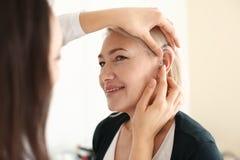 Facharzt für Hals- und Ohrenleiden, der Hörgerät in das Ohr der Frau auf hellen Hintergrund einsetzt stockfotografie
