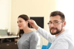 Facharzt für Hals- und Ohrenleiden, der zuhause Hörgerät in das Ohr der Frau einsetzt lizenzfreies stockbild