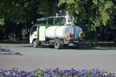 Fachkundige Fahrzeuge für Bewässerungsblumenbeete im städtischen p Stockbild