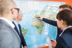 Fachleute, die Standorte auf Karte für globales Geschäft planen stockbild