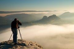 Fachmann auf Klippe Naturphotograph macht Fotos mit Spiegelkamera auf Felsen Träumerische Fogylandschaft, entspringen orange rosa Lizenzfreie Stockfotos