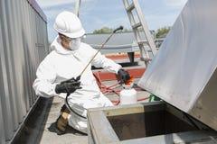 Fachmann in der schützenden Uniform, Maske, Handschuhe im Dach für das Säubern lizenzfreie stockfotos