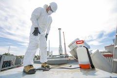 Fachmann in der schützenden Uniform, Maske, Handschuhe im Dach für das Säubern stockfoto