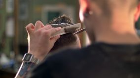 Fachmann tätowierte den Friseur, der seinem Kunden in einem Friseursalon einen neuen Haarschnitt gibt stock video footage