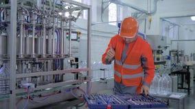 Fachmonteurmann im Sturzhelm und Arbeitskleidung, die Erneuerungsbetriebsausrüstung mit Spezialwerkzeugen nahe Gurtlinie tut stock footage
